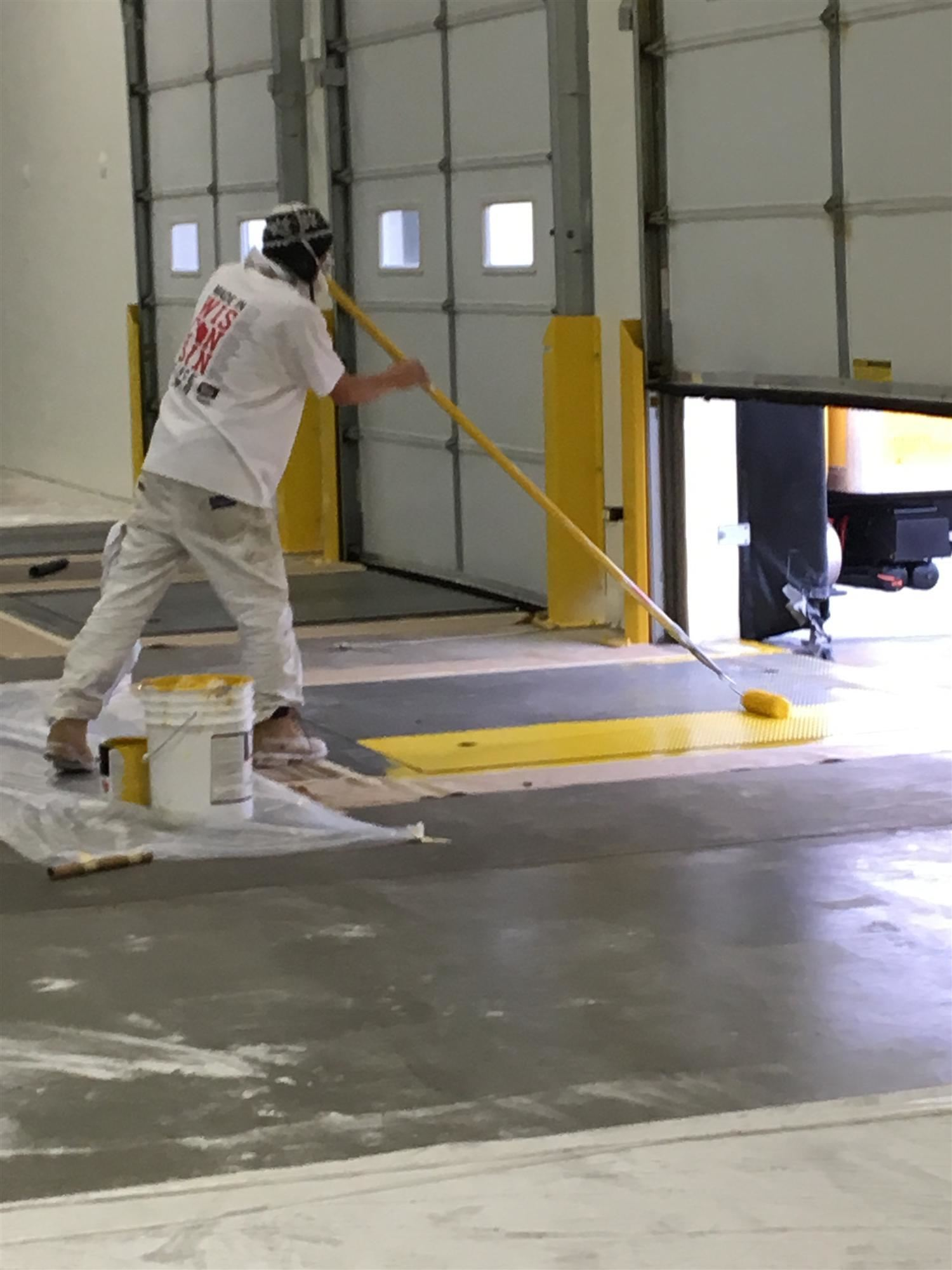 K2 painting contractor hard at work painting a loading dock safety yellow